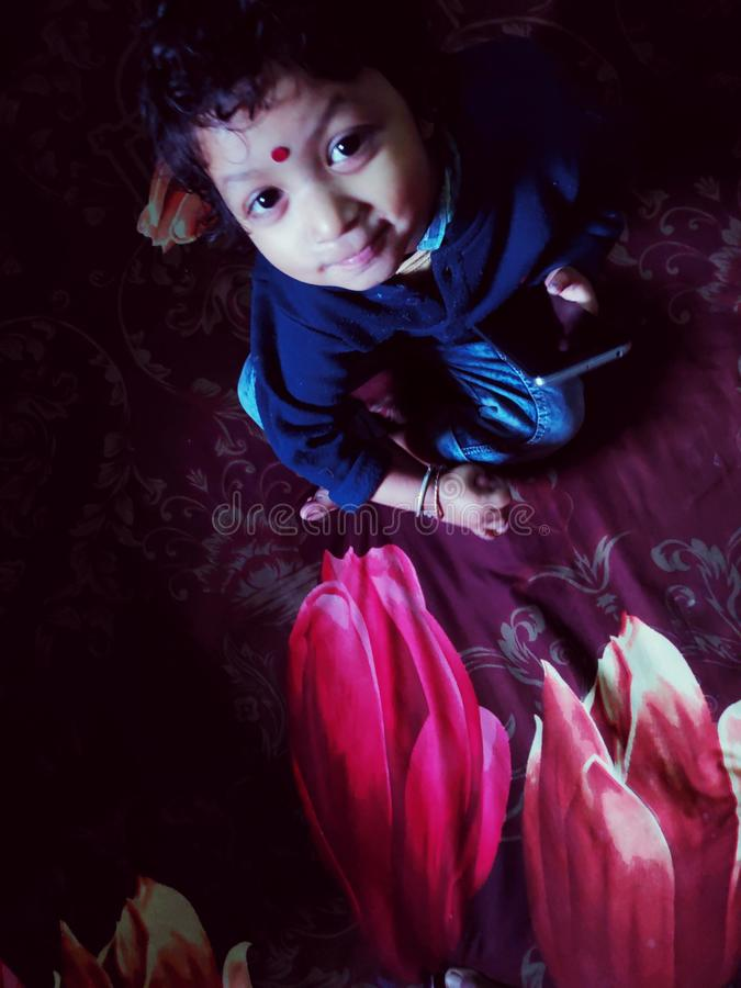 A face of 2 year old little girl who sitting on printed flowers. stock photos