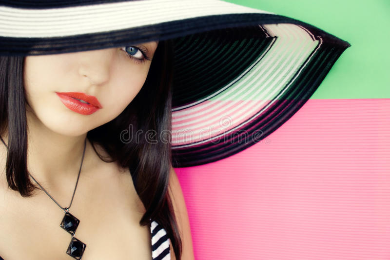 Face of young beautiful brunette in a summer hat royalty free stock image