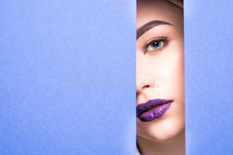 Face of young beautiful girl with a bright make-up and violet lips looks through a hole in violet paper. Closeup beauty portrait stock image