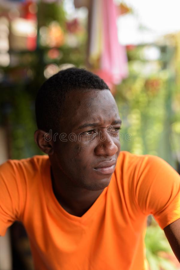 Face of young black African man thinking while looking at distan stock photography