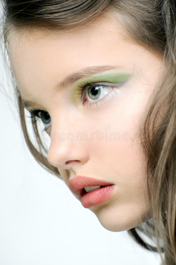 The face of a young girl with bright makeup on eyes. The face of a young girl with bright makeup on eyes on a light background royalty free stock photo