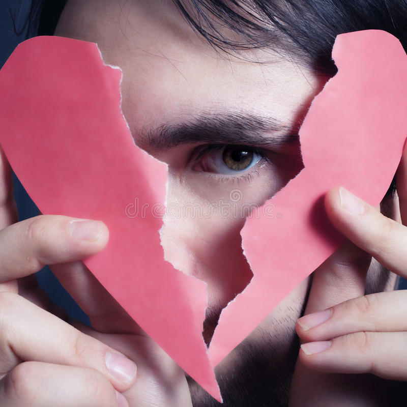 Face of young handsome man with broken paper heart royalty free stock photography