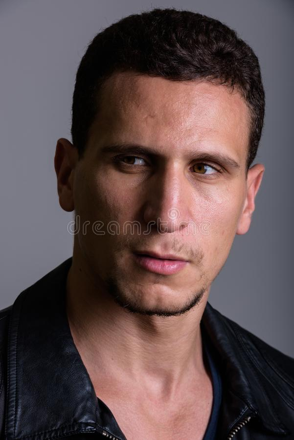 Face of young muscular Persian man thinking while looking suspic royalty free stock photos