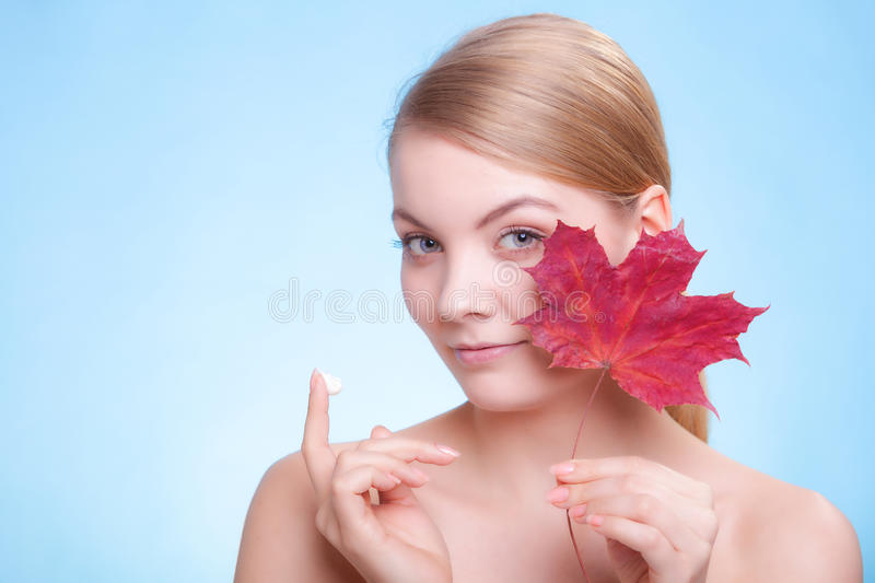 Face of young woman girl with red leaf and cream. Skincare habits. Face of young woman with leaf as symbol of red capillary skin on blue. Girl taking care of her stock images