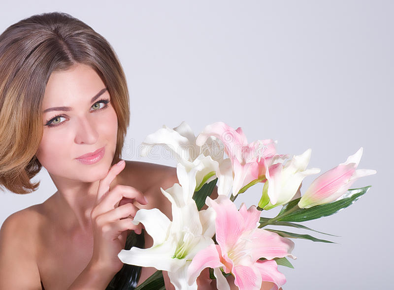 Face of the young woman with pink lily stock photography