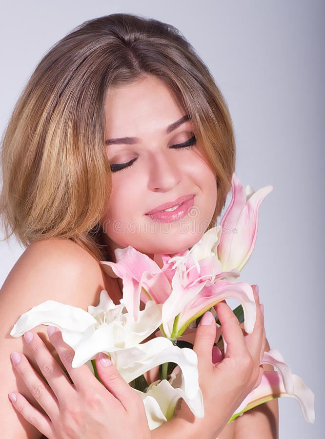 Face of the young woman with pink orchid royalty free stock photos