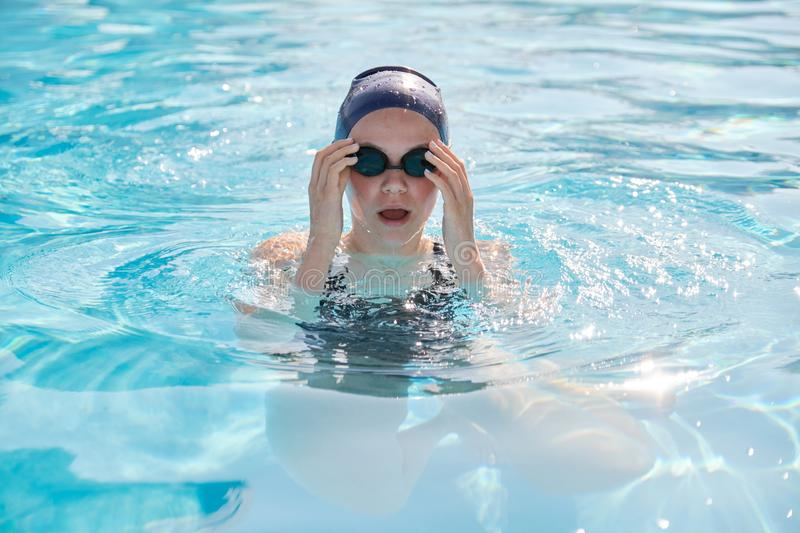 Face of young women swimmer in pool, girl in cap goggles for swimming stock photography
