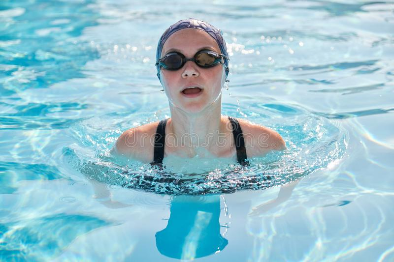 Face of young women swimmer in pool, girl in cap goggles for swimming royalty free stock images
