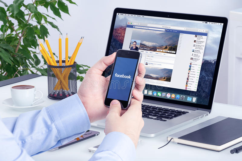 Facebook app en el iPhone de Apple y las favorables exhibiciones de la retina de Apple Macbook imagen de archivo