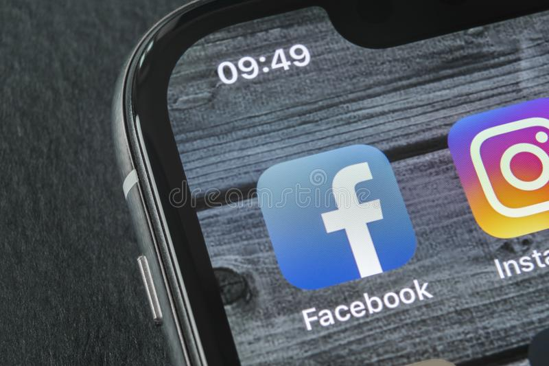 Facebook application icon on Apple iPhone X smartphone screen close-up. Facebook app icon. Social media icon. Social network royalty free stock image
