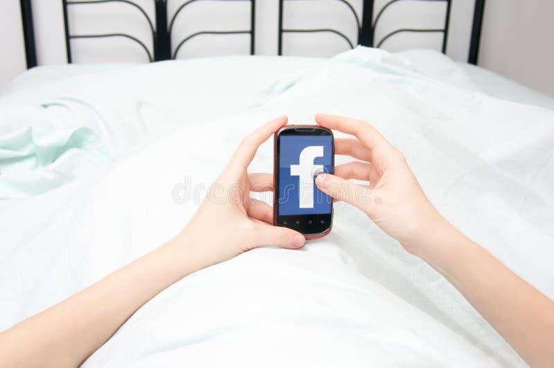 Facebook, das im Bett grast stockbilder