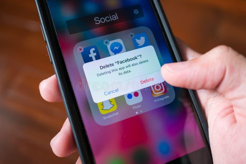 Facebook-gebruiker die Facebook-toepassing op iPhone 7 schrappen royalty-vrije stock afbeelding