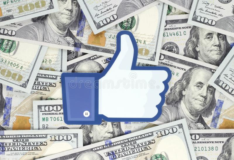 Facebook Like logo printed on paper, cut and placed on money background. Kiev, Ukraine - September 18, 2018: Facebook Like logo printed on paper, cut and placed royalty free stock image