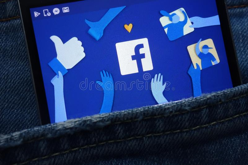 Facebook logo displayed on smartphone hidden in jeans pocket royalty free stock photo