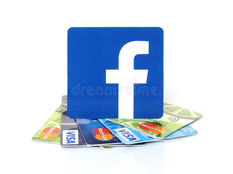 Facebook-Logo gedruckt auf Papier und auf Karten Visum und MasterCard gesetzt stockfotografie