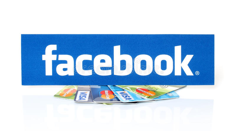 Facebook logo printed on paper and placed on cards Visa and MasterCard on white background stock images