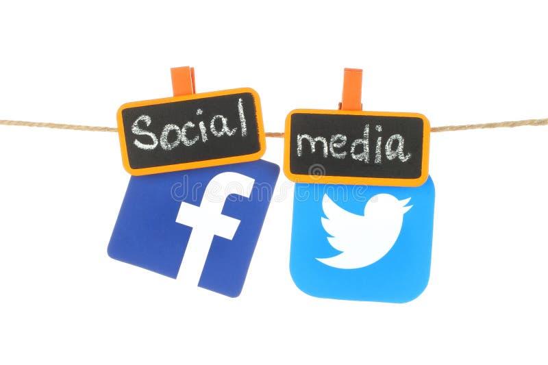 Facebook och Twitter logoer, hangind på ett rep royaltyfria foton