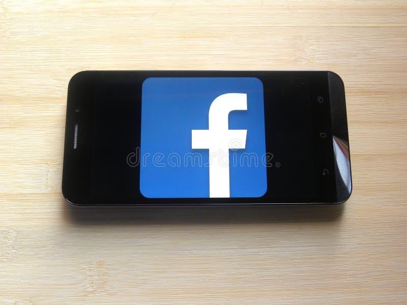 Facebook op smartphone stock afbeeldingen