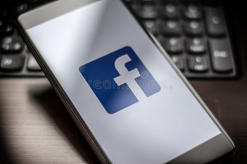 Facebook page on the smartphone on table royalty free stock images