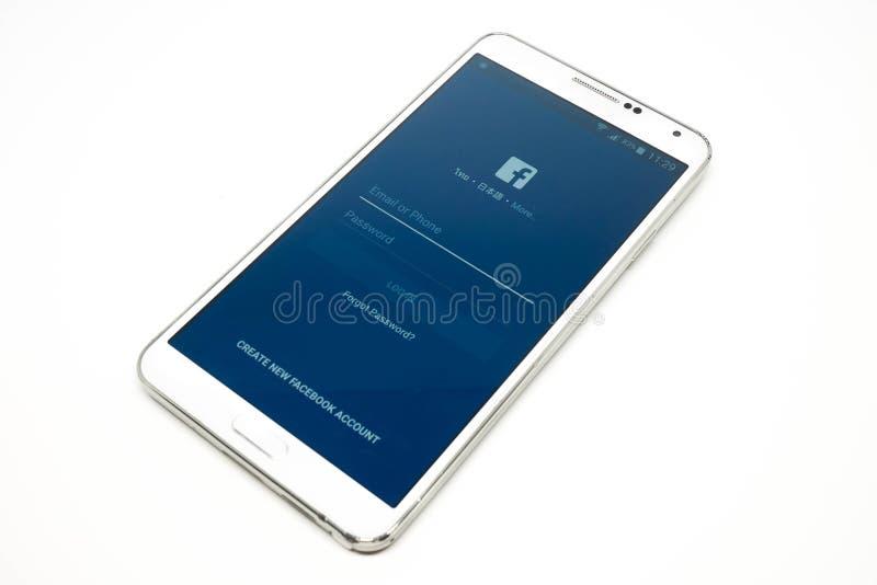 Facebook zastosowanie na białym telefonie komórkowym odizolowywającym zdjęcie royalty free