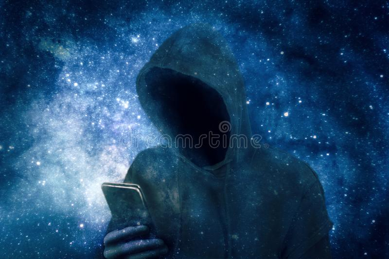 Cyber criminal in hoodie with smartphone. Faceless cyber criminal in hoodie with smartphone in front of bluish shimmering background stock image