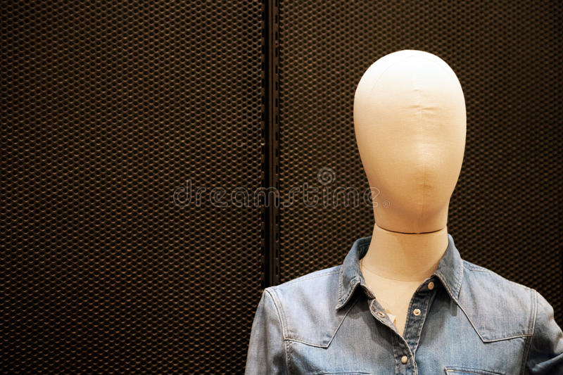 Faceless female mannequin wearing cheap casual jean jacket at shopping mall. Bald dummy close-up with copy space royalty free stock image