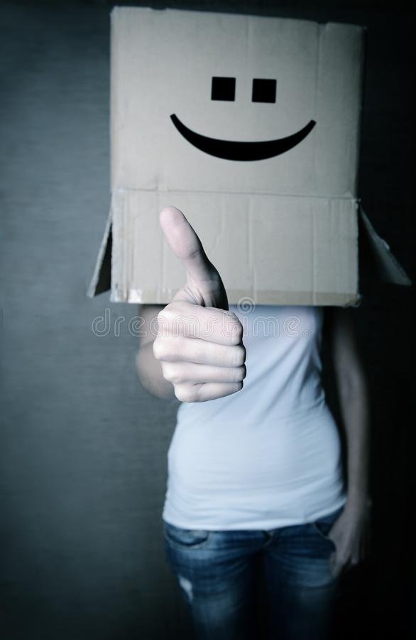 Faceless girl with box on her head LIKE with thumb up, social ne stock photo