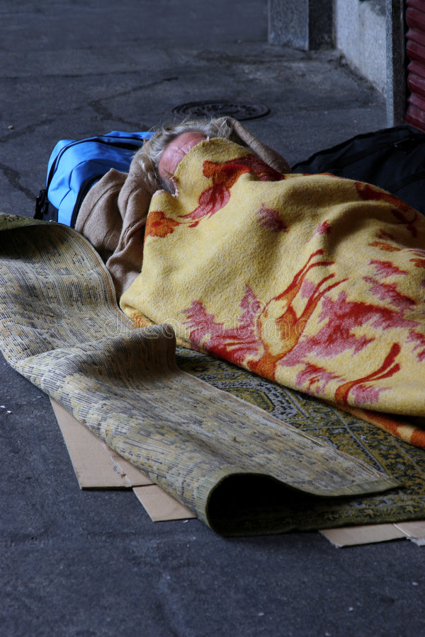 Faceless and homeless. Homeless man sleeping in the street stock photography
