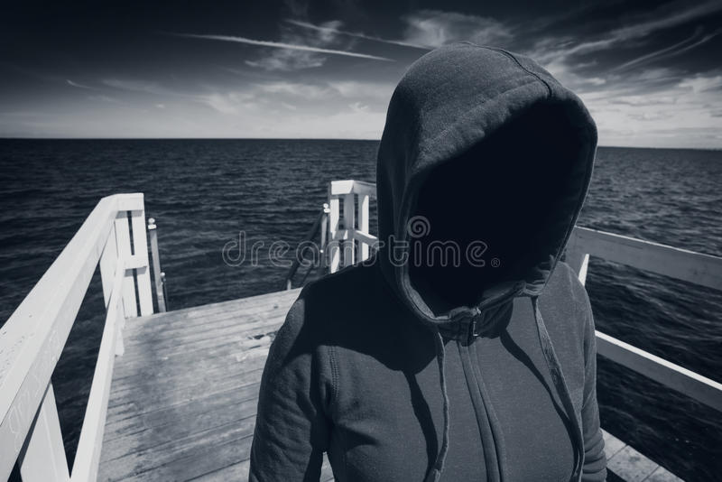 Faceless Hooded Unrecognizable Woman at Ocean Pier, Abduction Co royalty free stock image