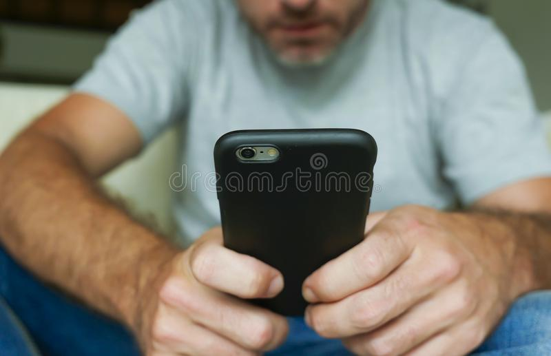 Hands of young man holding mobile phone sitting relaxed at home sofa couch using internet social media app on smartphone networkin. Faceless lifestyle portrait royalty free stock photography
