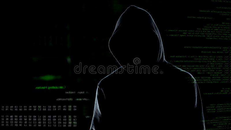 Faceless male hacker in hoodie standing in front of animated computer code stock photo