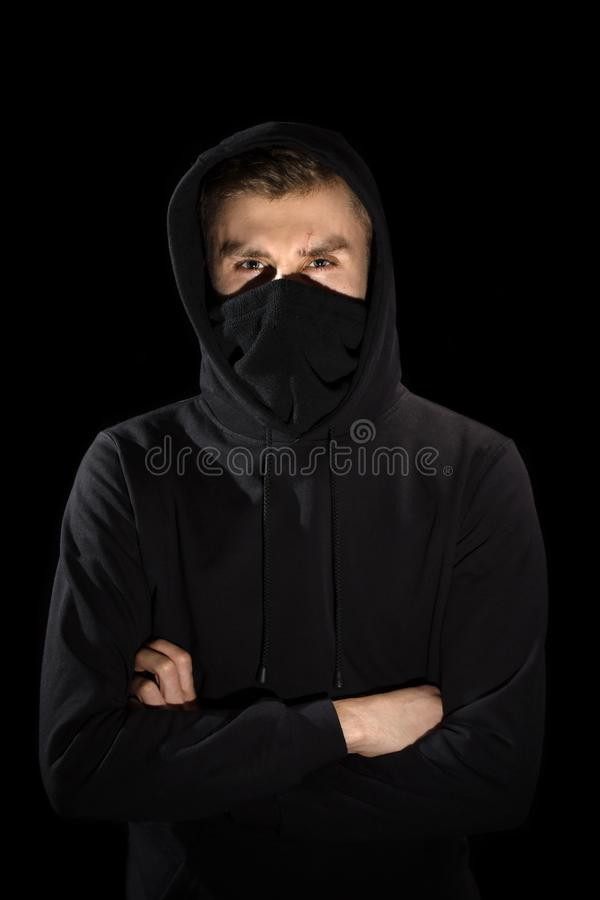 Faceless man with open eyes in hoodie standing  on black royalty free stock images