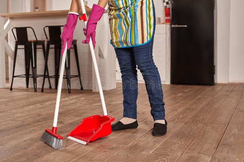Faceless middle section of young woman sweeping floor on the kitchen royalty free stock photography