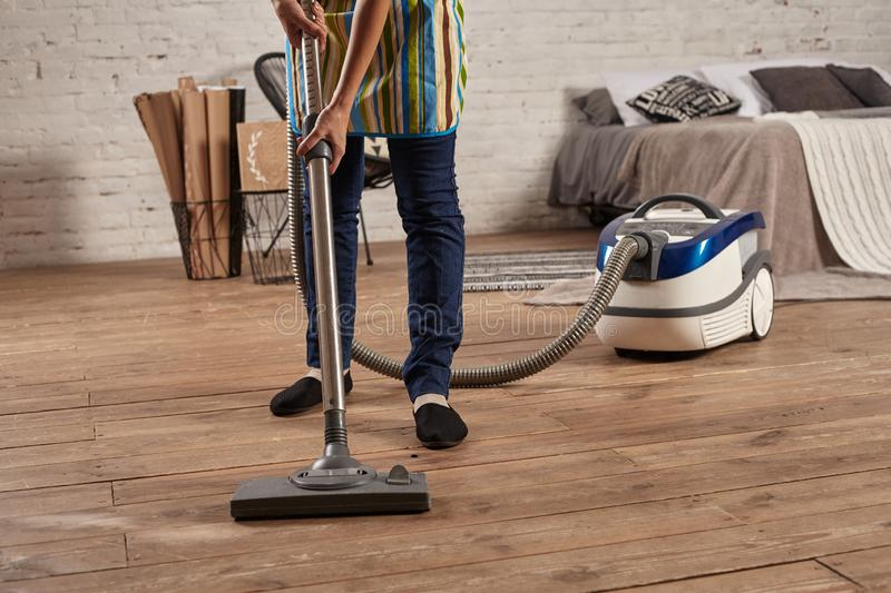Faceless middle section of young woman using vacuum cleaner in home living room floor, doing cleaning duties and chores stock photos