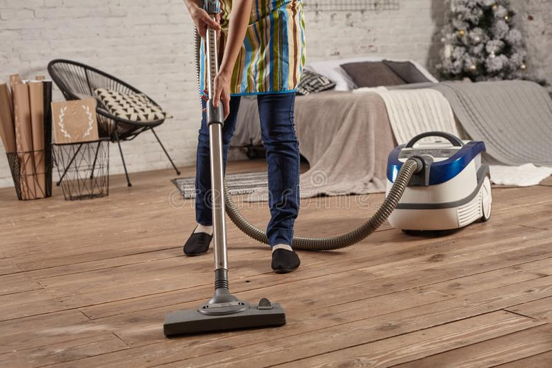 Faceless middle section of young woman using vacuum cleaner in home living room floor, doing cleaning duties and chores. Meticulous interior. Young female stock photo