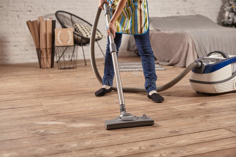 Faceless middle section of young woman using vacuum cleaner in home living room floor, doing cleaning duties and chores. Meticulous interior. Young female royalty free stock images