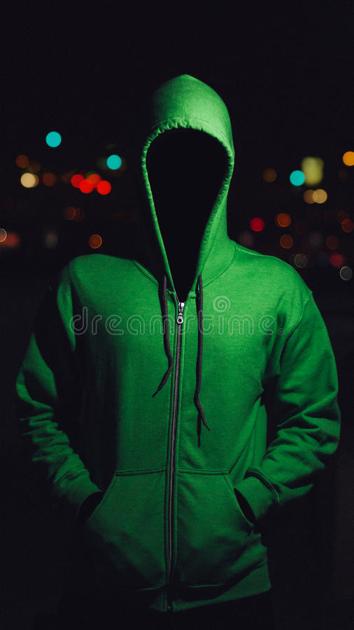 Faceless person in green hoodie stock images