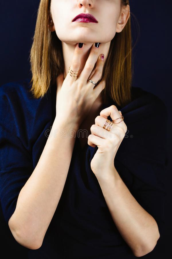 Faceless portrait of young adult white woman holding her hands with dark manicure on her neck stock image