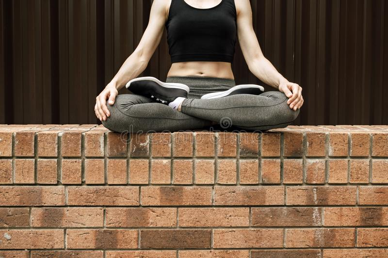 Faceless portrait of young female sitting in lotus position stock image