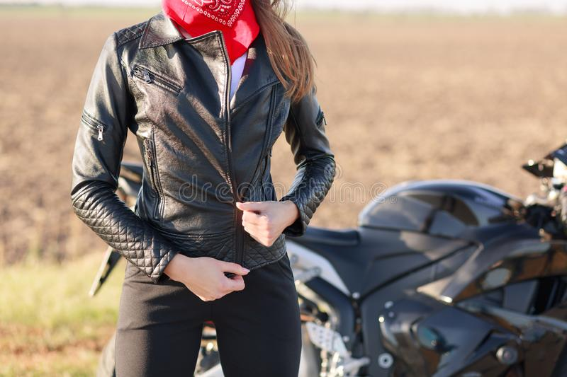 Faceless woman biker dressed in black clothes and red bandana on neck, keeps hand on her jacket, poses on road near her modern. Fast bike, stops her motobike royalty free stock photos