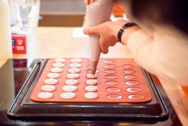 Facendo i macarons con la fine della borsa della pasticceria su immagine stock libera da diritti