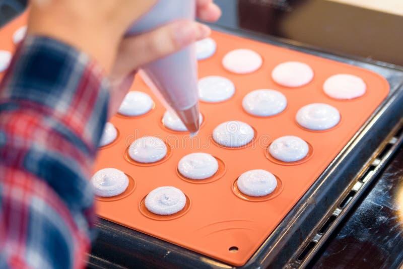Facendo i macarons con la fine della borsa della pasticceria su fotografia stock libera da diritti