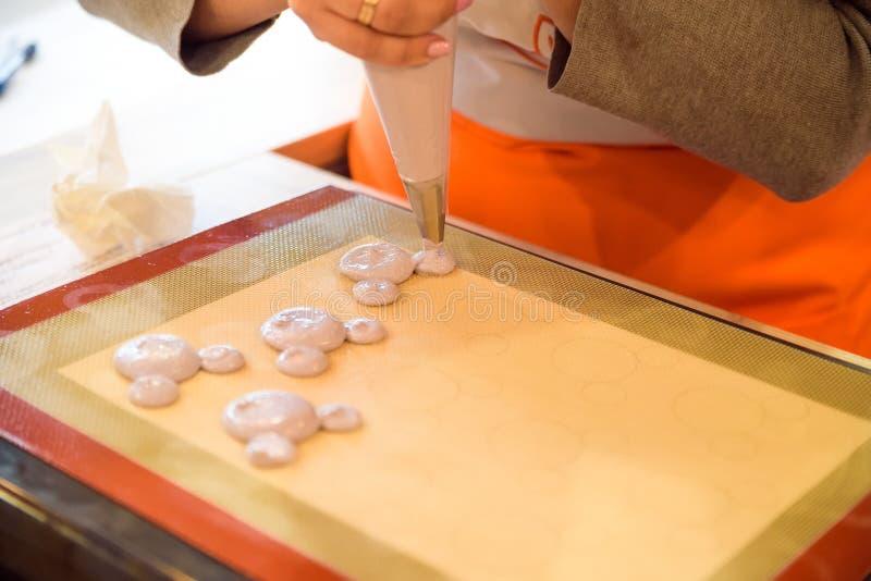 Facendo i macarons con la fine della borsa della pasticceria su fotografie stock libere da diritti