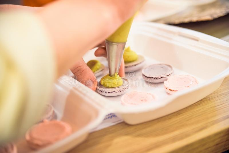 Facendo i macarons con la fine della borsa della pasticceria su fotografia stock