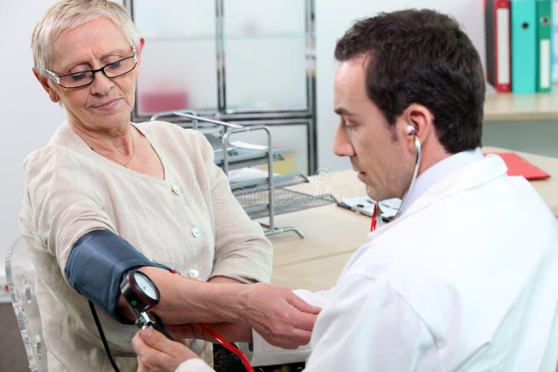 Facendo la sua prendere pressione sanguigna immagine stock