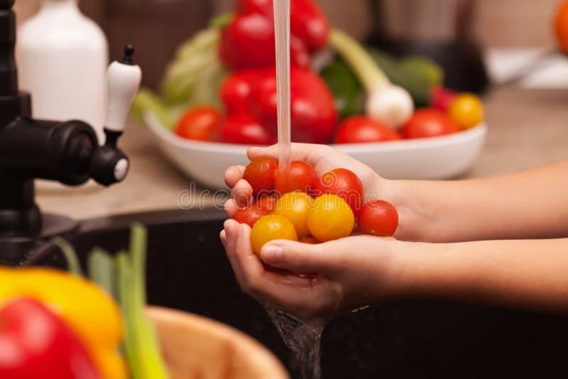 Facendo le verdure insalata, lavante gli ingredienti - pomodori ciliegia fotografia stock