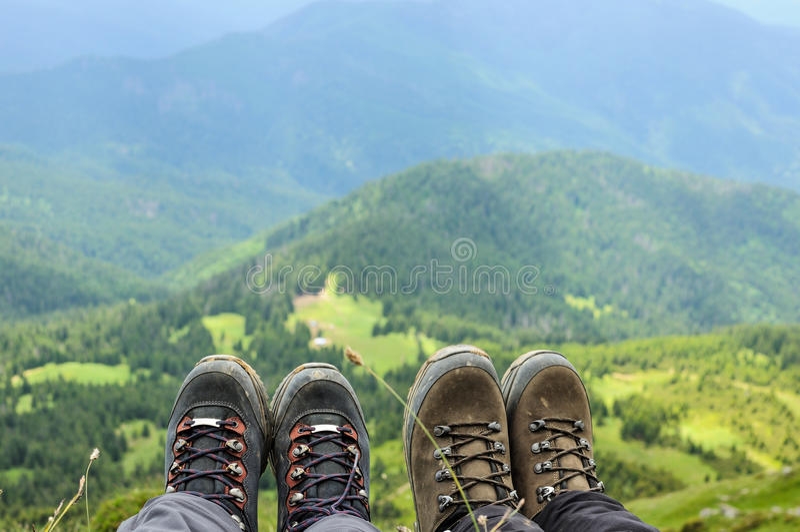 Facendo un'escursione gli stivali del viaggiatore che si siedono sull'alta montagna completano fotografie stock