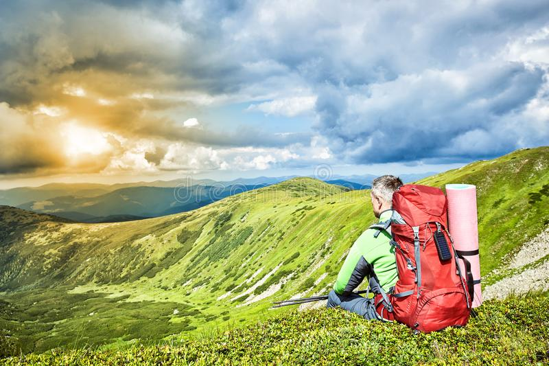 Facendo un'escursione nelle montagne di estate con uno zaino immagine stock