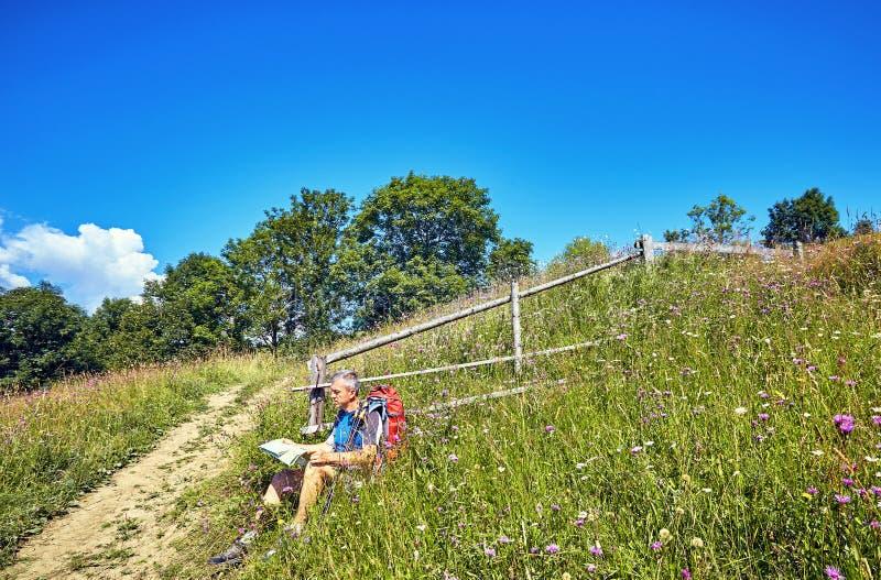 Facendo un'escursione nelle montagne di estate con uno zaino immagine stock libera da diritti