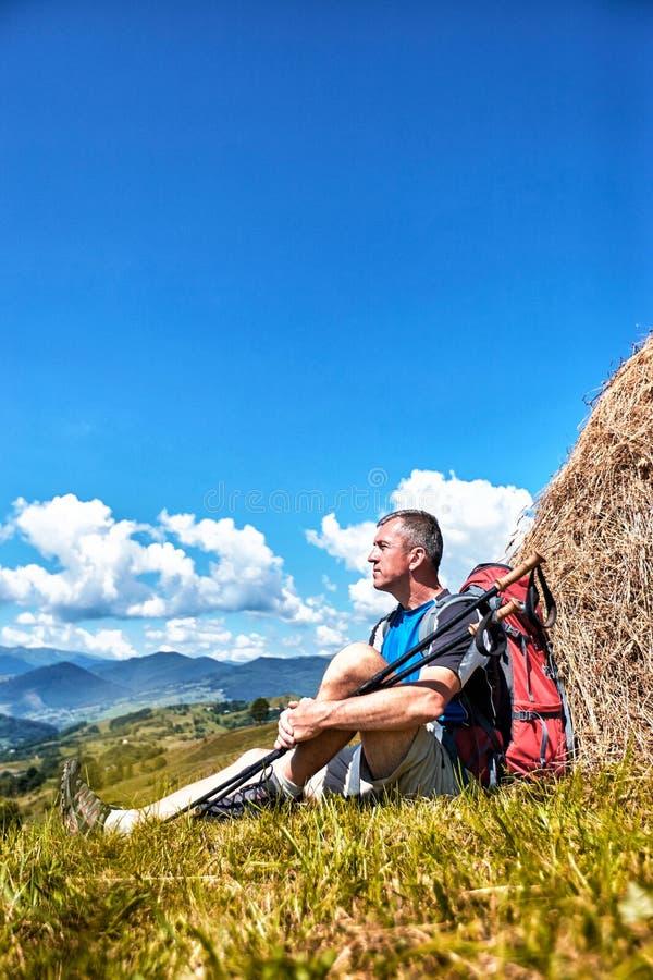Facendo un'escursione nelle montagne di estate con uno zaino immagini stock libere da diritti